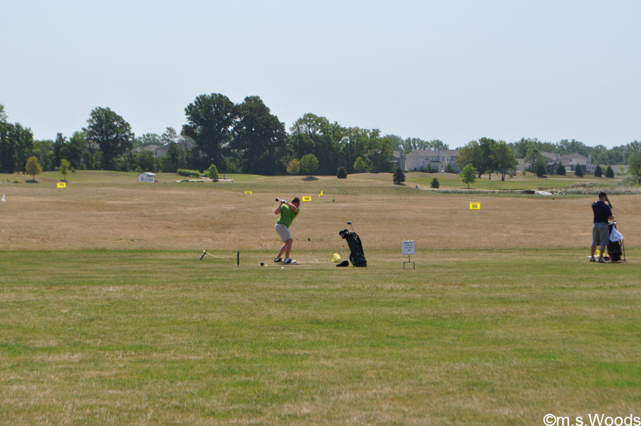 A Golfer Takes a Swing at the Driving Range